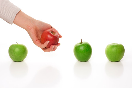 Picking different apple among other similar on white