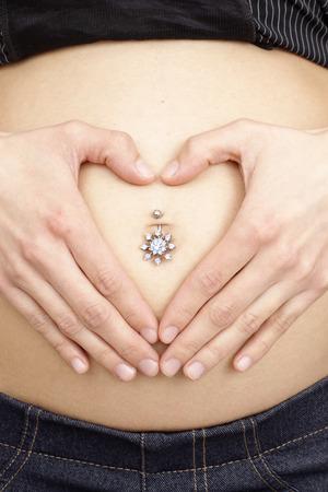 ombligo: panza embarazada de la mujer adolescente joven con la perforaci�n en el ombligo Foto de archivo