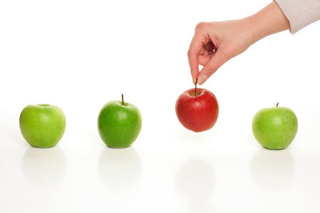 Picking different apple among similar on white Stock Photo