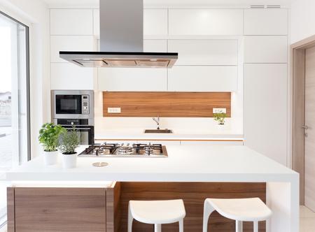 kitchen island: Modern elegant white kitchen with walnut island