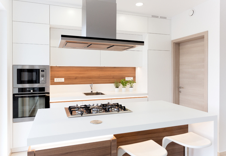 Modern elegant white kitchen with walnut island