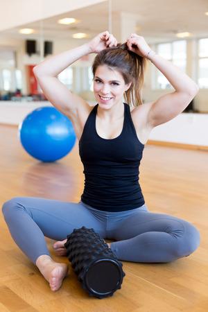 Feliz ajuste young womanin el gimnasio sentado en la pelota Foto de archivo