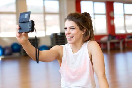 Young fitness vlogger with camera capturing herself