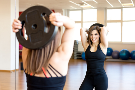 brunette woman: happy fit young woman in the gym lifting plate