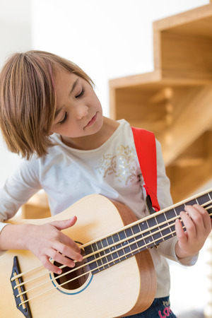 smal: Little girl practicing playing small bass guitar