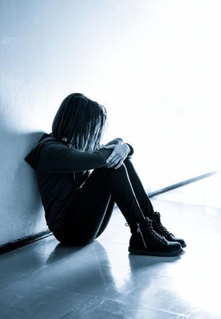 ホールに座っている悲しい十代女の子 写真素材