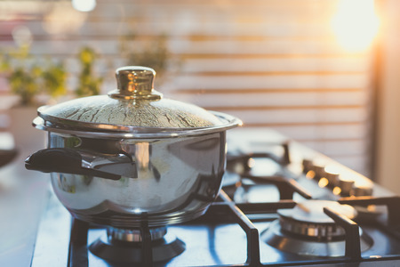 Boiling water in the pot on the stove in the evening Foto de archivo