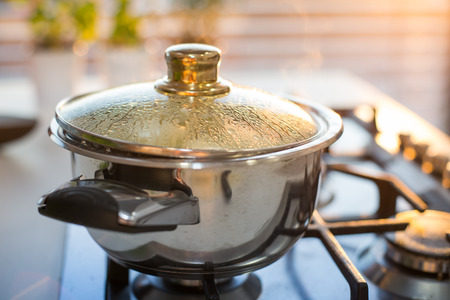 stovetop: Boiling water in the pot on the stove in the evening Stock Photo