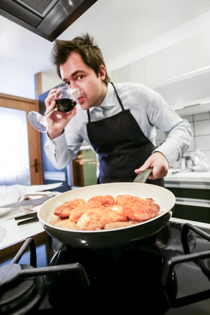 home cooking: Male chef at home cooking with wine