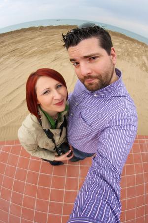 Funny couple taking fisheye selfie on the beach Stock Photo