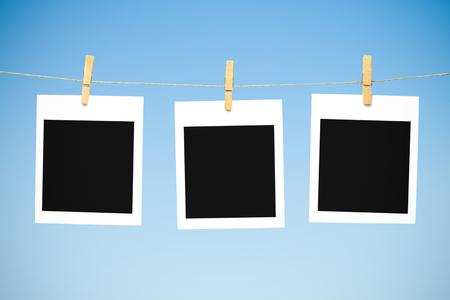 blank spaces: Three blank polaroid photos against blue sky
