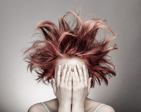 Frightened woman with messy hair hiding photo