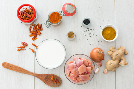 Ingredients for modern spicy chicken curry on wooden desk Stock Photo