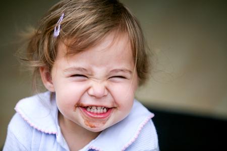 dientes sucios: Hermosa niña haciendo rostro divertido después de comer chocolate