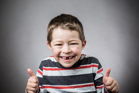 즐거운 어린 소년 이빨없는 미소로 웃고