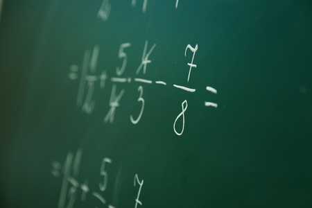 Calcualting with fractions on green blackboard at primary school