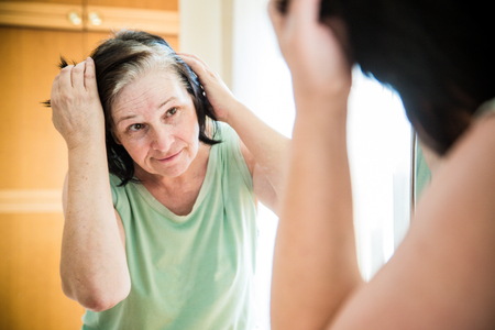 careless: Senior woman checking her gray hair in the mirror Stock Photo