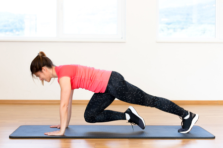 Active young woman exercising at the gym