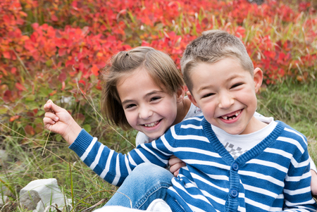 Little siblings smiling in beautiful autumn nature