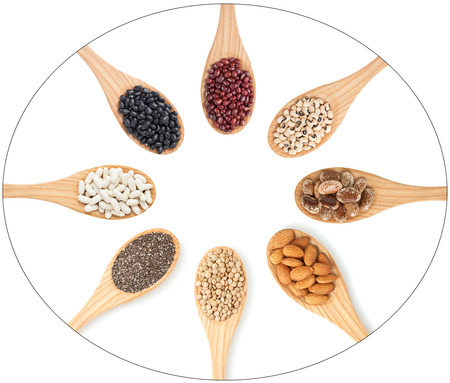 Grains, seeds and legumes on wooden spoons  Stock Photo