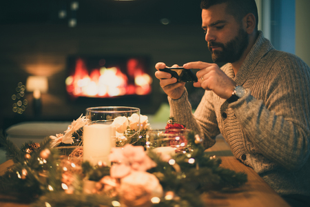 Bearded man taking a photo of decorated christmas table