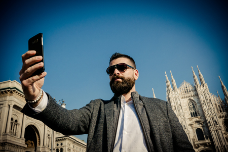 Bearded adult male turist taking selfie in Milano