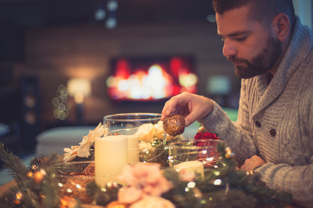 Bearded man decorating christmas table with bubbles Foto de archivo