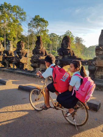 Siem Reap, Cambodia - DECEMBER 29, 2017: Two cambodian children in uniforms going to school by bike