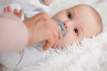Few months old baby boy on soft white blanket