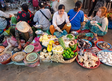 SIEM REAP, CAMBODIA - December 30th, 2017: Cambodian people selling food in the market of Siem Reap in difficult conditions.