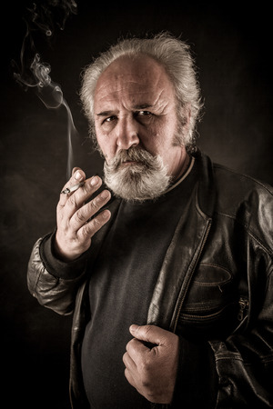 Grumpy senior man smoking cigarette against dark background Stock Photo