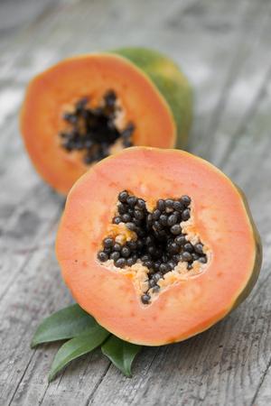 Cut papaya fruit on wooden background