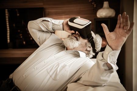 Senior bearded man with VR glasses in modern home 版權商用圖片