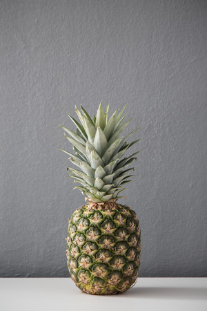 Pineapple on the table against gray wall 版權商用圖片