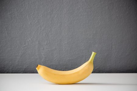 Banana on white table against grey wall