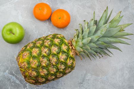Pineapple, mandarines and apple on the stone 版權商用圖片