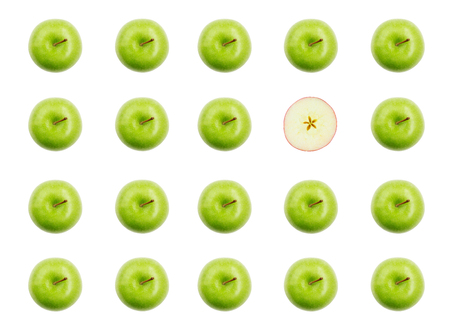 Stand out of the crowd concept with green apples and one cut apple overhead view 版權商用圖片