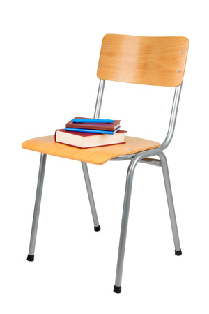 Typical school chair and books isolated on white