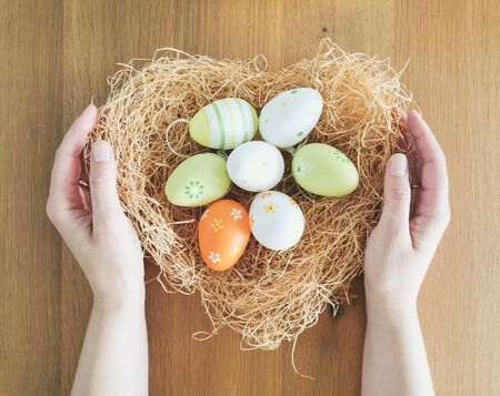 Female hands gently holding heart shaped nest with easter eggs