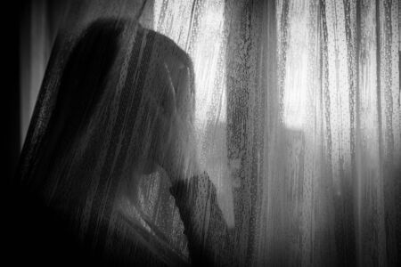 Depressed woman looking through window during quarantine due to domestic violence, social distancing or physical problem