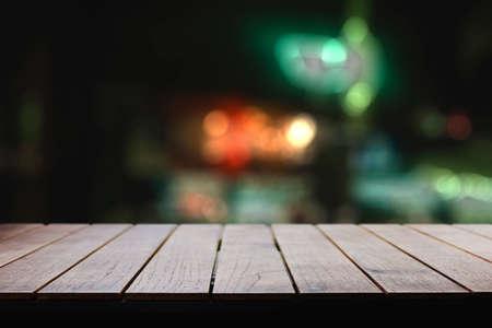 Empty wooden table in evening restaurant Foto de archivo