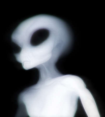 Grey alien illuminated as he passes through dimensions Stock Photo