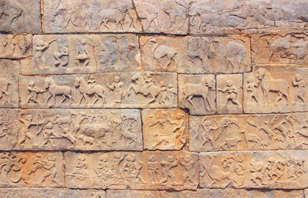 Wall with a carved relief  scenes of hunting and life ancient indian people  photo