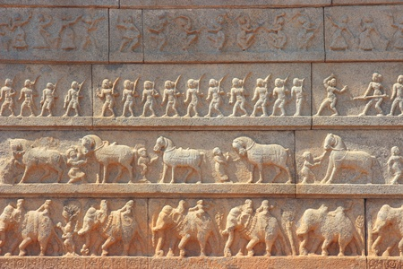 Wall with a carved relief  big ancient Indian army with horses and elephants photo