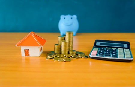 Blue pig bank and coins stack and yellow paper house for money saving concept
