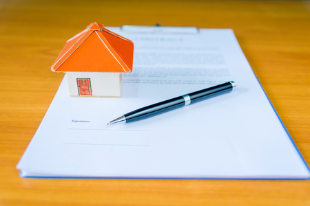man signing paperwork, new home in background
