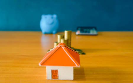 A piggy bank put on the stacking gold coins and blackboard house and clock on the vintage blue background, saving money for buy a new real estate or loan for planned investment in the future concept. 免版税图像