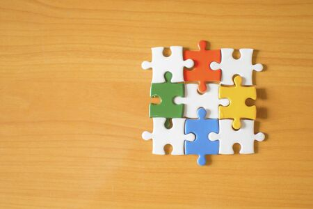 four jigsaw puzzle couple of pieces on wood texture background empty copy space for inscription or objects. business, education concept.red, green, blue,yellow,Orange Reklamní fotografie
