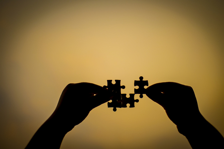 Silhouette of a hand holding a jigsaw puzzle piece isolated with sunset backgroun