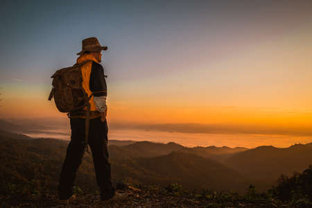 Young man hiker on a top of a mountain standing on top of cliff in summer mountains at sunset and enjoying view of nature 免版税图像